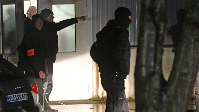 Policemen stand in front of a refugee camp during a search in Emmerich, Germany, on Dec. 22.