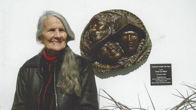 """Local acclaimed artist Ernie Lee Miller stands in front of her bronze sculpture """"Cultures Under the Sun"""" which is at the entrance of the Tularosa Basin Museum of History Saturday, Jan. 28."""
