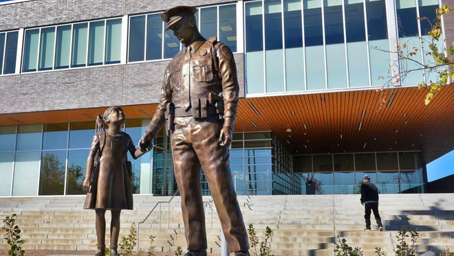 A statue of a police officer helping a little girl stands outside the St. Cloud Police Department Thursday, Oct. 23 as a man walks up the stairs and goes inside.