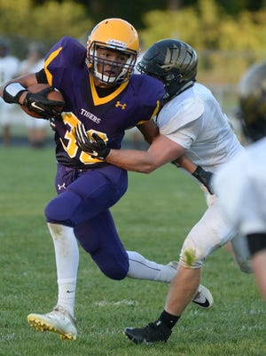 Hagerstown's Jalen Oliver carries the football as Winchester's Jonathan Thornburg makes a tackle in Winchester in September 2016.