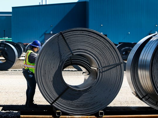 A workers inspects rolls of steel outside one of several building that makes up the new Big River Steel mill in Osceola, Ark.