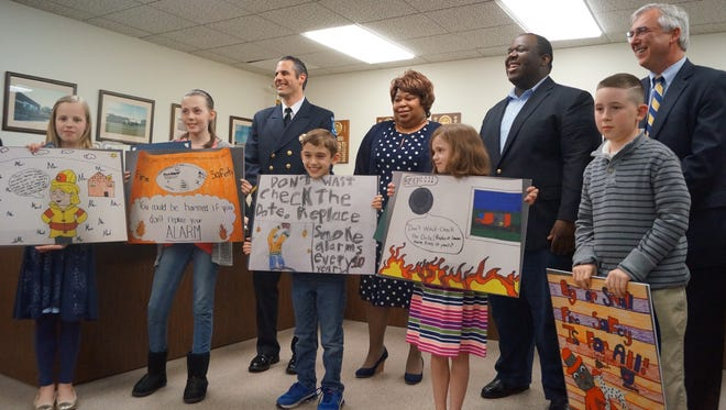 Local winners from the Mount Laurel School District in a Fire Safety Poster Contest include (left to right, front row): Genevieve Slota, Hillside School; Tessa Sellers, Hartford School; Kyle Gonzalez, Countryside School; Lauren Jolicoeur, Hillside School and Salvatore Neri, Parkway School. Behind them are Mount Laurel Fire Marshal Brian McVey (left), the contest coordinator; Tamara and Daryl Lloyd from Farmers Insurance, corporate sponsors of the local contest and Mount Laurel School District Superintendent of Schools George J. Rafferty.
