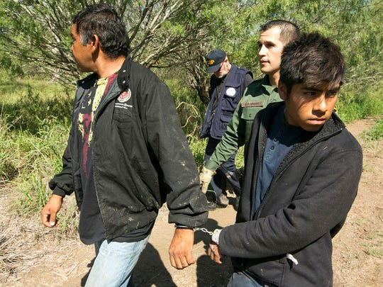 Border Patrol Agent Roberto Rodriguez escorts two Mexican nationals apprehended near the Texas-Mexico border on Oct. 12, 2017.