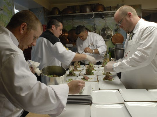 From left: Reuben Sliva, David Funaro, Richard Montoya, and Shannon Yates plate the Braised Jamison Farm Rack of Lamb with Morel Mushroom and English Pea La Nage and Blackberry Pan Sauce which they served at the dinner they prepared  at the James Beard House in New York City July 24, 2006. (Photo by Rohanna Mertens)