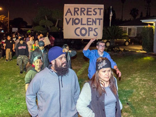 Protesters march towards the off-duty officer's home in Anaheim, Calif., Wednesday, Feb. 22, 2017. A Los Angeles policeman is under investigation after a video appears to show him firing a single round during an off-duty tussle with a 13-year-old boy. No one was injured but two teenagers were arrested after the incident, which spurred dozens of people to protest against police Wednesday night in the streets of Anaheim, where the officer lives and the confrontation occurred.