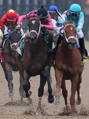 Monomoy Girl, right, with Florent Geroux aboard, bumps Wonder Gadot, with John Velazquez to win the 144th Running of the Kentucky Oaks.