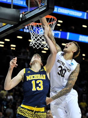 Notre Dame forward Zach Auguste (30) defends a shot by Michigan forward Moritz Wagner (13) in the first half. Michigan vs Notre Dame in Round 1 of the NCAA Tournament the Barclay Center in Brooklyn, New York on Mar. 18, 2016. 