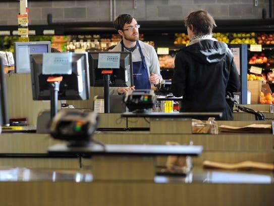 Three Rivers Market employee Cody Clark, left, helps