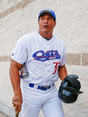 Jose Canseco walks out to the field before a game with the United League's Forth Worth Cats.