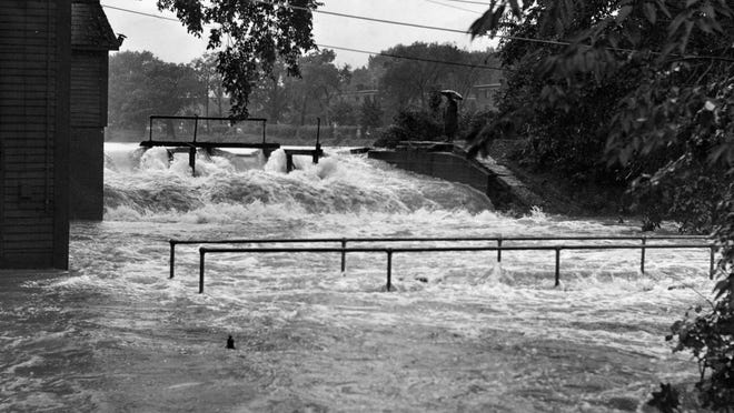 Flood waters rage across catwalk at Coes Pond dam in 1955.