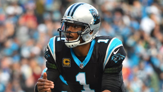 Carolina Panthers quarterback Cam Newton (1) pretends to light a candle on top of the football after scoring a touchdown in the fourth quarter at Bank of America Stadium.