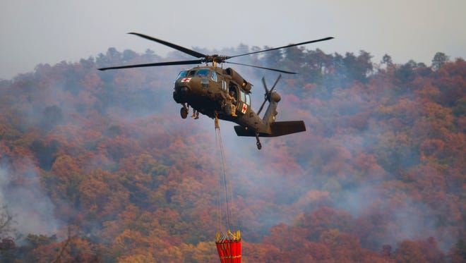 Nov 18, 2016; Blount County, TN, USA;    An Air National Guard helicopter retrieves water from the Little River before dropping it on a wildfire in Blount County near Walland Elementary School. Mandatory Credit: Caitie Mcmekin/Knoxville News Sentinel via USA TODAY NETWORK