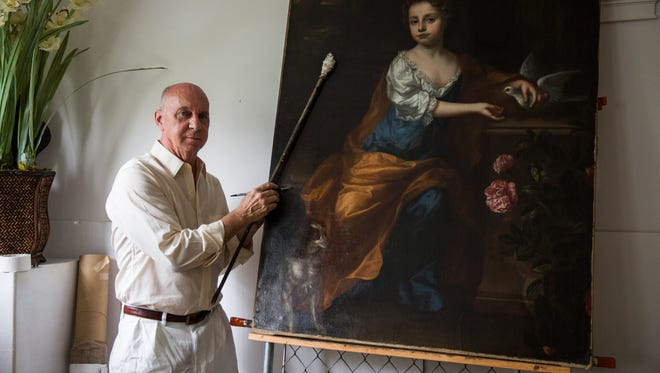 Painting conservator and restorer Tom Wagner poses for a portrait with a piece from the 1680's he recently restored at his work studio in Naples, Fla. on Thursday, May 16, 2018.