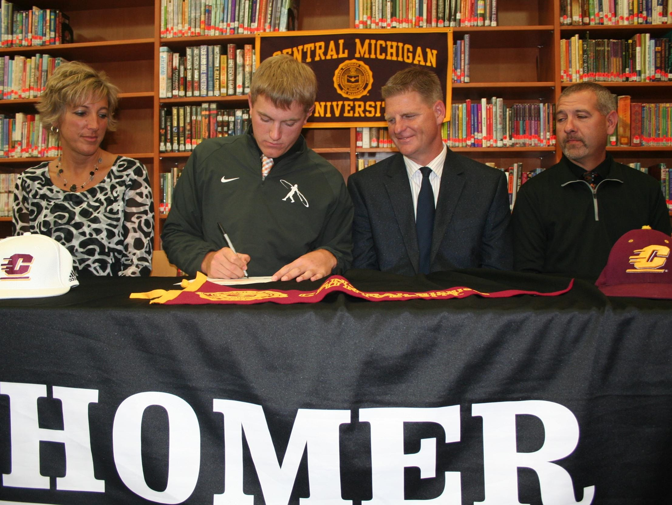 Homer's Brock Ridgeway signs to play baseball at Central Michigan. He is joined by his parents Lisa and Rob Ridgeway and Homer coach Scott Salow.