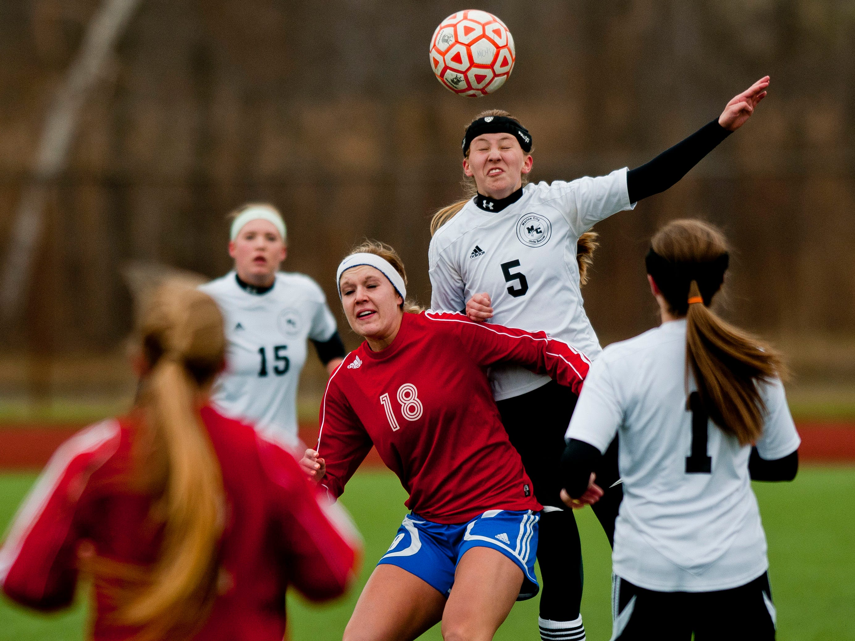 Marine City's Emilie Andrews heads the ball over St. Clair's Mackenzie Kent during a soccer game Wednesday at East China Stadium.