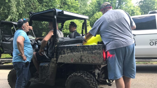 Emergency crews fill an all-terrain vehicle with supplies for the Licking County Dive and Rescue Team on Sunday afternoon as they search for a possible drowning victim off Claypool Road SE.