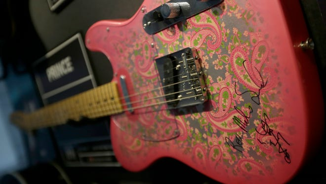 """A guitar signed by Prince from his Dec. 17, 1997, """"Jam of the Year"""" tour is up for auction. The signature included his symbol when he was the artist formerly known as Prince."""