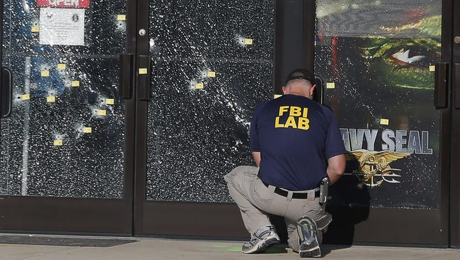 An FBI investigator works to gather evidence outside a military recruiting center on July 17 in Chattanooga, Tennessee. Muhammad Youssef Abdulazeez of Hixson, Tennesee., attacked two military facilities on Thursday, in a shooting rampage that killed four Marines.