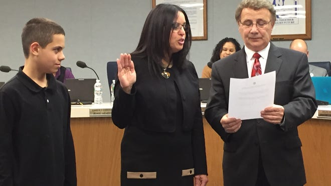 Inez Acosta is sworn in to serve on the Vineland Board of Education on Wednesday by board Solicitor Bob DeSanto (right) while with her son, Jake Cruz, looks on.