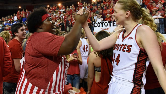 Kayla Johnson celebrates with USD's #44 Abigail Fogg after the Coyotes win the WNIT championship game against FGCU at the DakotaDome in Vermillion, S.D., Saturday, April 2, 2016.