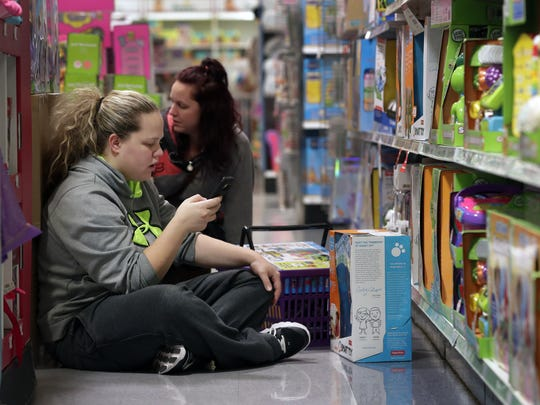 Crystal, left, and Whitney Johnson of Appleton research their next stop while shopping at Toys R Us during Black Friday in Grand Chute.