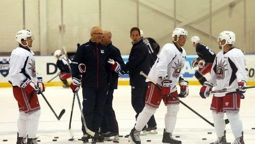 Rangers players and coaches gather at practice during training camp.
