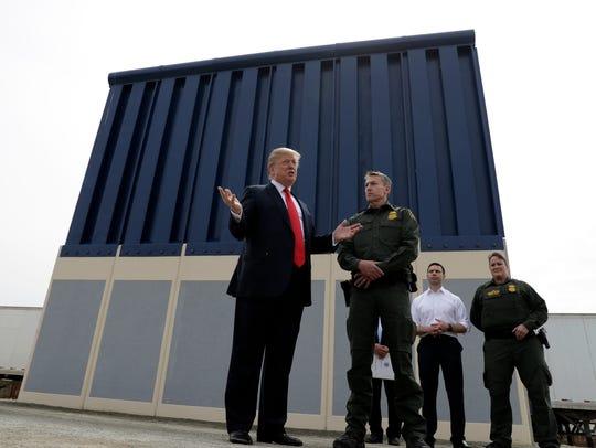 President Donald Trump reviews border wall prototypes,