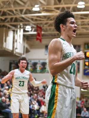 Floyd Central's Cobie Barnes yells as teammate Luke Gohmann celebrates in the background after Barnes drew the foul and basket during the Highlanders' 49-47 win over New Albany Friday evening. It was the Highlanders' first win over New Albany in boys basketball since 2003.