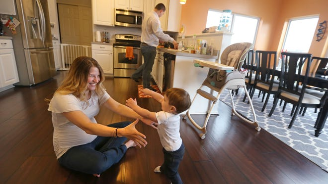 Katie D'Arcy plays with son JJ, 11 months, as husband John D'Arcy starts dinner in their home in Henrietta Thursday. Katie is due with their second child in June.