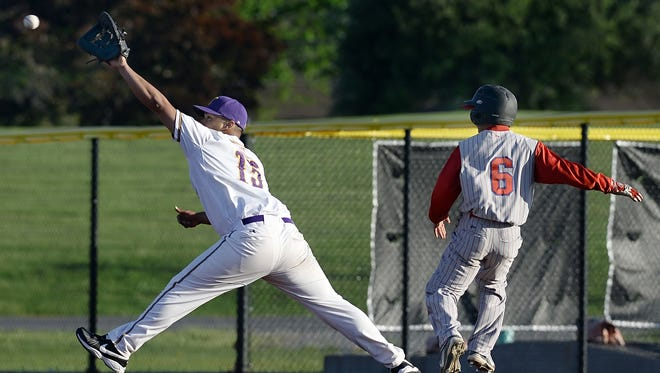East High first baseman Keylis Serrata, left reaches for the ball as Monroe's Elis Rosado touches the bag during RCAC championship game played at Monroe Community College on Thursday, May 14, 2015.