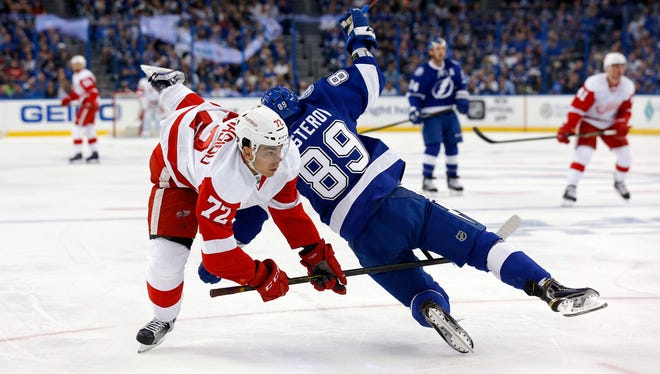 Red Wings forward Andreas Athanasiou is upended by the Lightning's Nikita Nesterov during the first period of the Wings' 3-2 loss in Game 1 of the Eastern Conference quarterfinals Wednesday in Tampa, Fla.