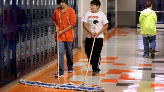 Eighth graders James Meyer, left, and Chris Reyes at Blackman Middle School sweep the hallway of the school in 2014 as part of the school's 1,000 Acts of Kindness program.