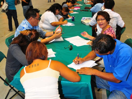 In this May 2009 file photo, job seekers fill out employment