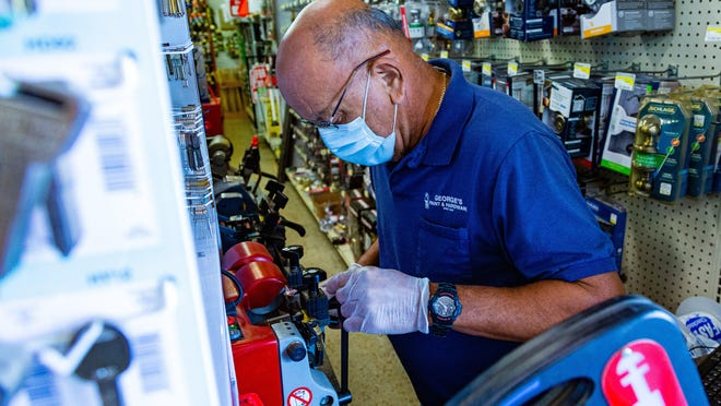 Diego Perez cuts a key for a customer at George's Hardware on Dixie Highway in West Palm Beach on April 2.