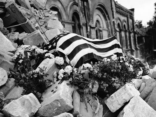 Shrouded by Old Glory, and piled high with flowers, the body of an America officer, identified as Major Howie, lies among the ruins of the church in Holy Cross in St. Lo, France on July 24, 1944.
