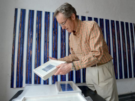 Artist Robert Stuart handles newly framed pieces of his artwork in his studio overlooking West Beverley Street in downtown Staunton on Friday morning, August 8, 2014. Stuart will be exhibiting his work at Staunton-Augusta Art Gallery from Aug. 15 to Sept. 20.