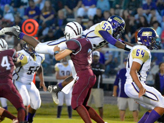Waynesboro's Tyshawn Brooks dives through the air past Stuarts Draft's Garrett Campbell during their game against Stuarts Draft High School played in Stuarts Draft on Friday, Sept. 12, 2014.
