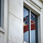 The Mississippi state flag is reflected in a window of the Public Employee Retirement System building in downtown Jackson.
