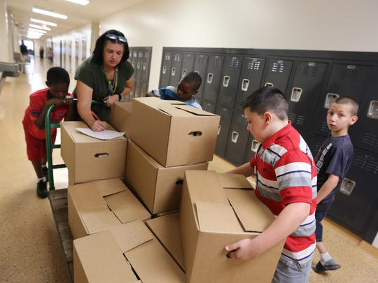 Tawanna Applegate, a para professional at Oyler School, gets assistance from students delivering Power Packs from the Freestore Feedbank to students at Oyler School in Lower Price Hill. During the school year, the packs go to 175-200 students on Fridays to feed the kids over the weekend.