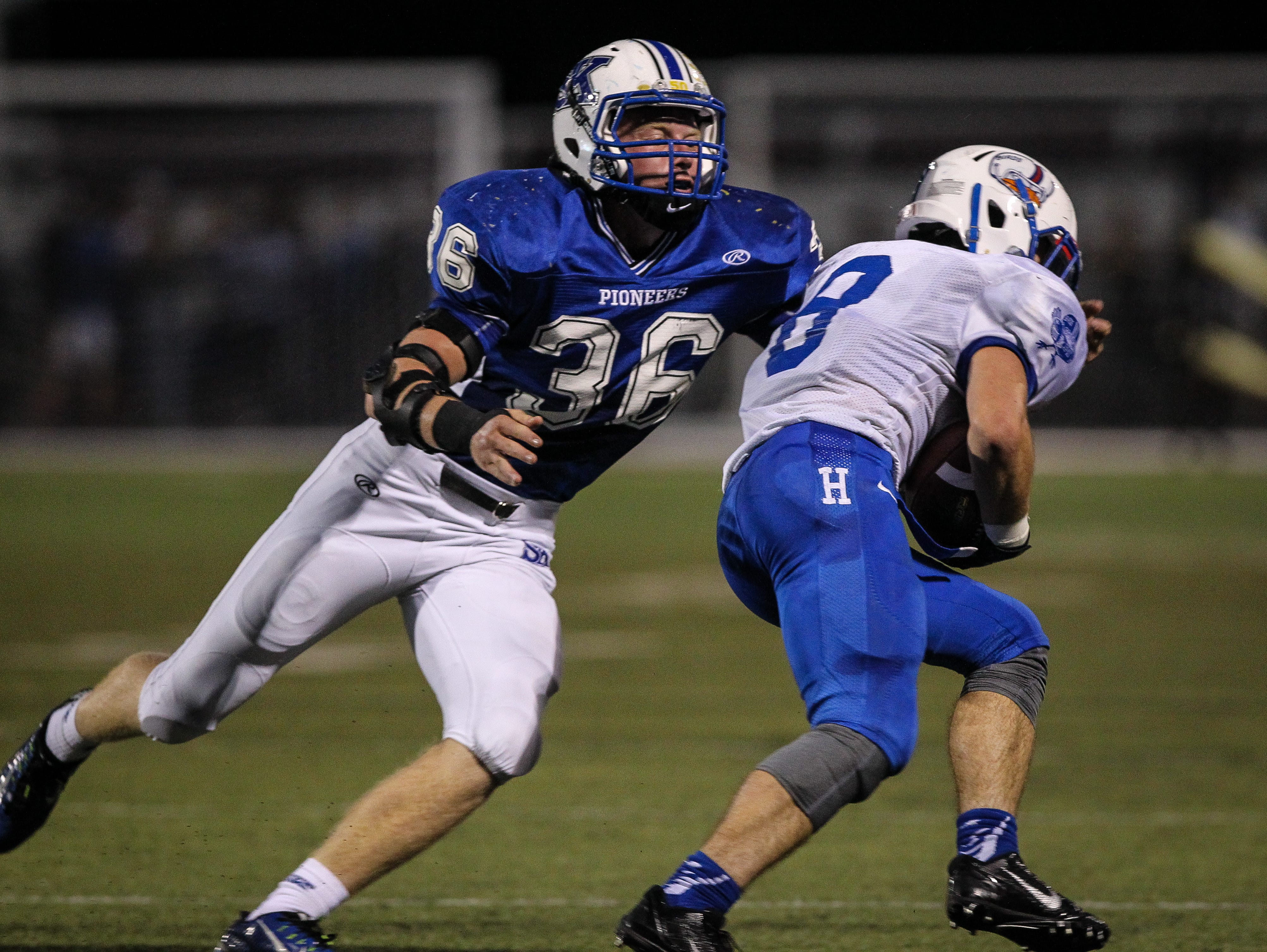 Simon Kenton's Taylor Holtkamp looks to wrap up Highlands' Nick Kendall during their game Friday, September 25, 2015.