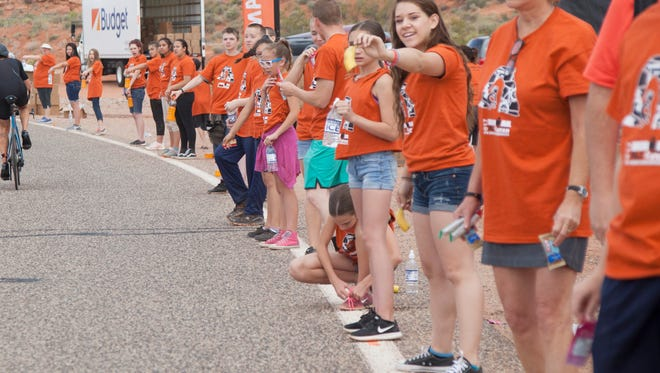 Volunteers lined up along Washington Parkway offer assistance to passing bicyclists during the St. George Ironman 70.3 on Saturday, May 6, 2017.
