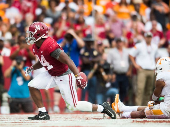 Alabama running back Damien Harris (34) runs into the