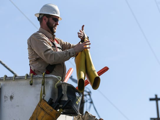 AEP lineworker Danny Lester removes protective gear after replacing a fuse on a power pole.