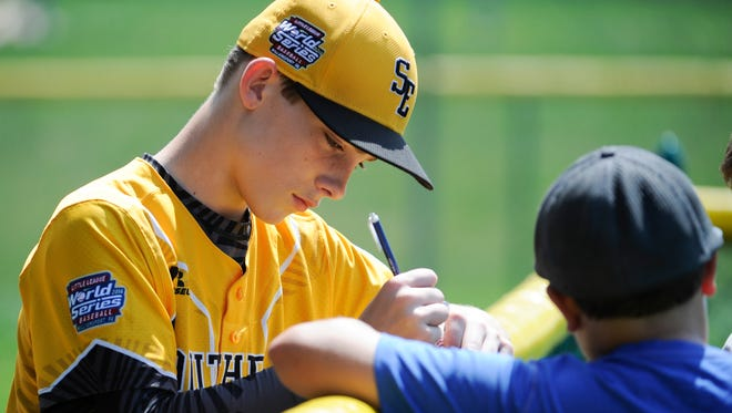 Goodlettsville 's Tanner Jones signs an autograph for Troy Dineen, 10, of Wilmington, Del., before Goodlettsville faces Maine-Endwell (N.Y.) in the U.S. championship baseball game at the Little League World Series in South Williamsport, Pa., Saturday, Aug. 27, 2016.