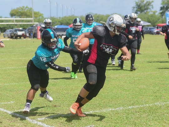 Sindalu's Lavana Terlaje (12) pursues Leticia Blas of the Lady Raiders during their Bud Light Guam Women's Tackle Football League game at the University of Guam field on April 28, 2018.