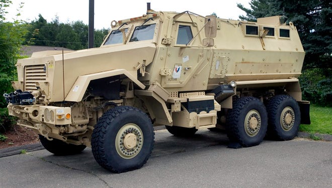 A mine-resistant, ambush-protected vehicle sits in front of police headquarters in Watertown, Conn.