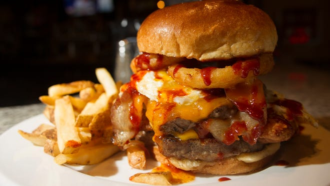 2 Dogs Pub's challenge burger is seen on Tuesday, July 22, 2014. The burger includes two Angus beef patties, breaded tenderloin, bacon, two fried eggs, cheddar cheese, onion rings and hot sauce.