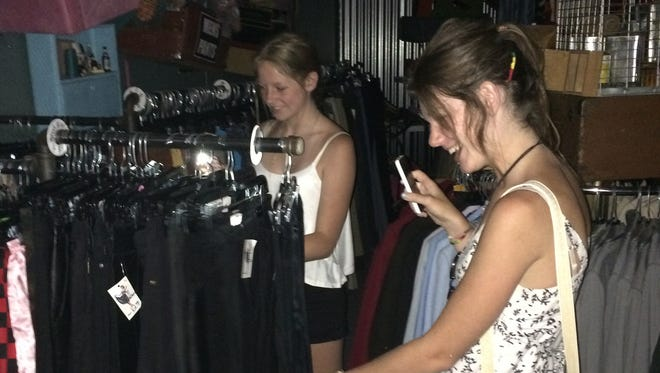 Shoppers use the flashlight apps on their phones Saturday to shop at Junkee Clothing Exchange in Reno. Power failed mid-morning for more than 1,800 customers, including part of the Midtown commercial corridor.