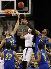 Delaware forwards Skye Johnson (left) and Maurice Jeffers defend a shot by Charleston's Payton Hulsey in the first half during an opening round game of the CAA tournament Friday in Baltimore.