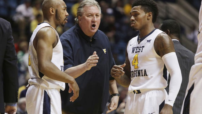 West Virginia coach Bob Huggins gives instructions to guards Daxter Miles Jr. (4) and Jevon Carter (2) during the second half of the team's NCAA college basketball game against Coppin State, Wednesday, Dec. 20, 2017, in Morgantown, W.Va. (AP Photo/Raymond Thompson)